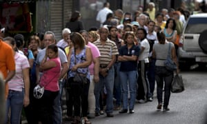 Shoppers queue outside of a supermarket in downtown Caracas, Venezuela. Venezuelans continue to struggle to find basic goods including detergent and sugar.