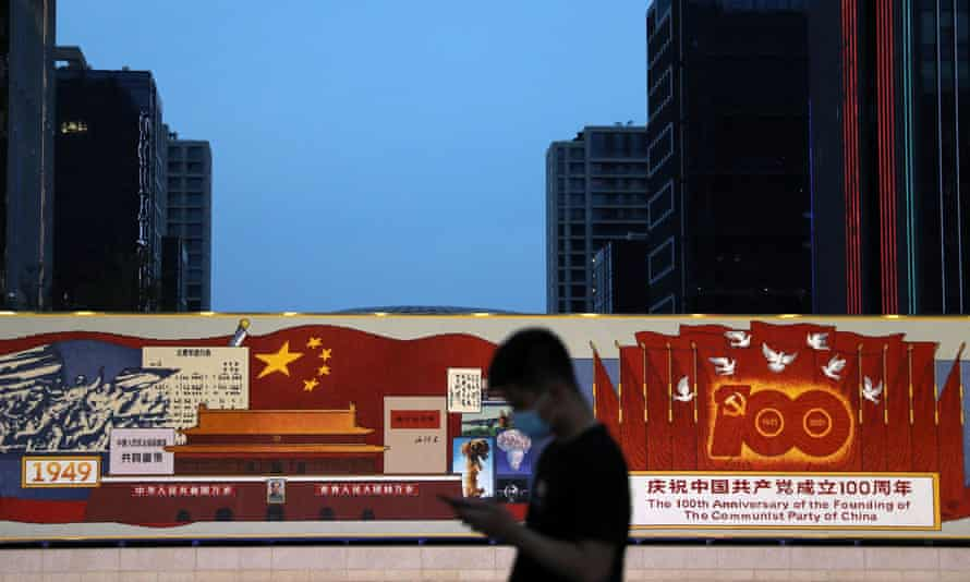 A man walks past a decorated board with images of Tiananmen Gate and Chinese national flag, marking the 100th founding anniversary of the CCP in Beijing
