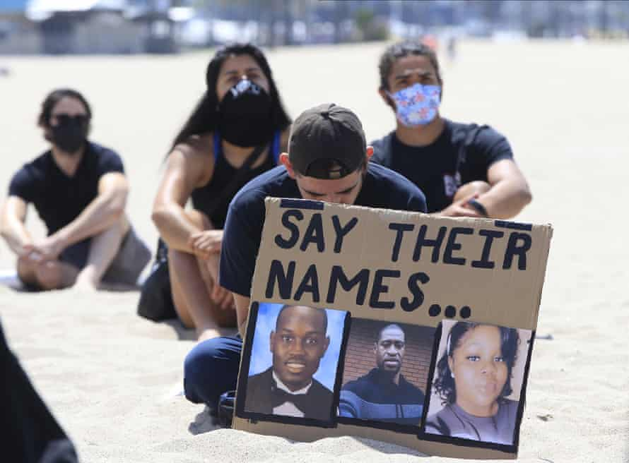 People sit during a moment of silence at a Black Lives Matter protest, in the Venice Beach area of Los Angeles, 12 June 2020.