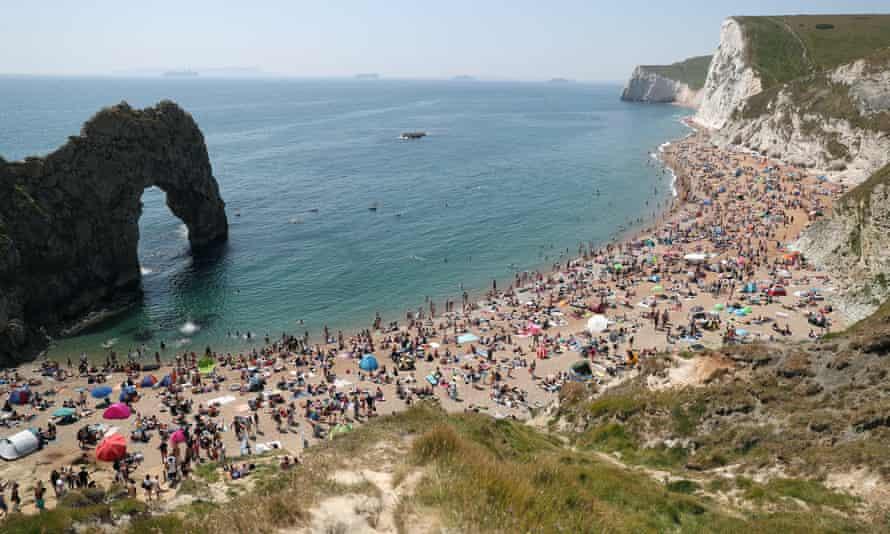 Beach heaving with people.
