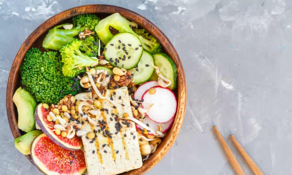 Buddha bowl with tofu, broccoli and vegetables in a wooden bowl
