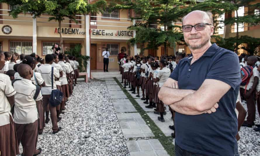 Artists for Peace and Justice founder Paul Haggis stands outside the APJ Academy with students during the daily morning assembly.