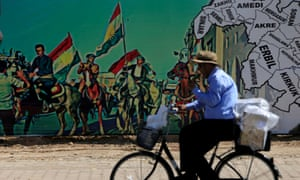 A man rides a bike near a mural supporting the referendum for independence of Kurdistan in Erbil on 24 September 2017.