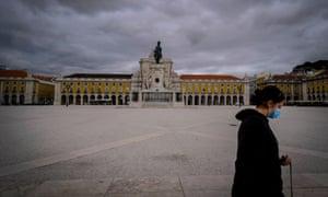 A woman walks through Comercio Square in Lisbon