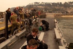 People fleeing the fires at Mallaccota board an Australian navy landing craft to be evacuated.
