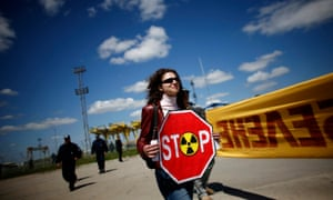 An anti-nuclear demonstrator protests outside the gates of a plant.
