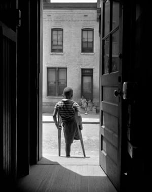 Washington DC, young boy standing in the doorway of his home on Seaton Road in the northwest section. His leg was cut off by a streetcar while he was playing in the street. June 1942