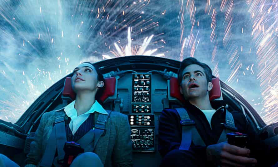 Gal Gadot and Chris Pine in  a futuristic vehicle, looking up through its canopy at fireworks exploding around them