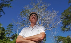 Nelson Kroll, manager of Madaracre forestry concession in Madre de Dios, stands in front of a Shihuahuaco tree