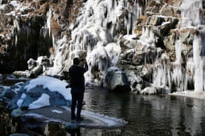 A man takes a photograph of a partially frozen waterfall in the Tangmarg area of Srinagar, India