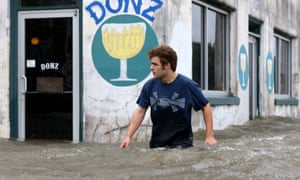 Logan Courvlle walks in front of a flooded business in Mandeville, Louisiana, on Saturday.