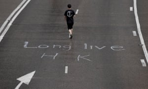 """A protester wearing a t-shirt with the words """"Revolution"""" walks past writings the word """"Long Live HK"""" in Hong Kong on Monday, July 1, 2019."""