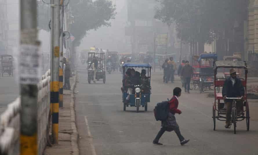 A schoolgirl crosses a road shrouded in haze in New Delhi, India