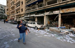 A woman carries a child past damaged shops