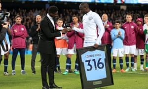 Yaya Toure receives a presentation from his brother Kolo after the final whistle