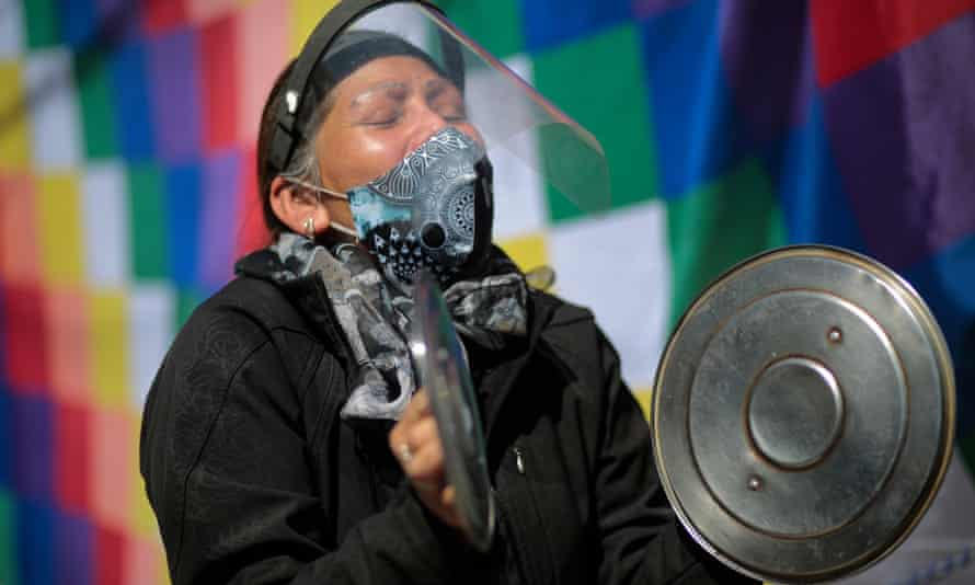 A demonstrator makes noise with pan lids at a protest in La Paz, Bolivia.