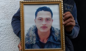 Walid Amri holds a photo of his brother Anis outside the family house in Oueslatia, Tunisia.