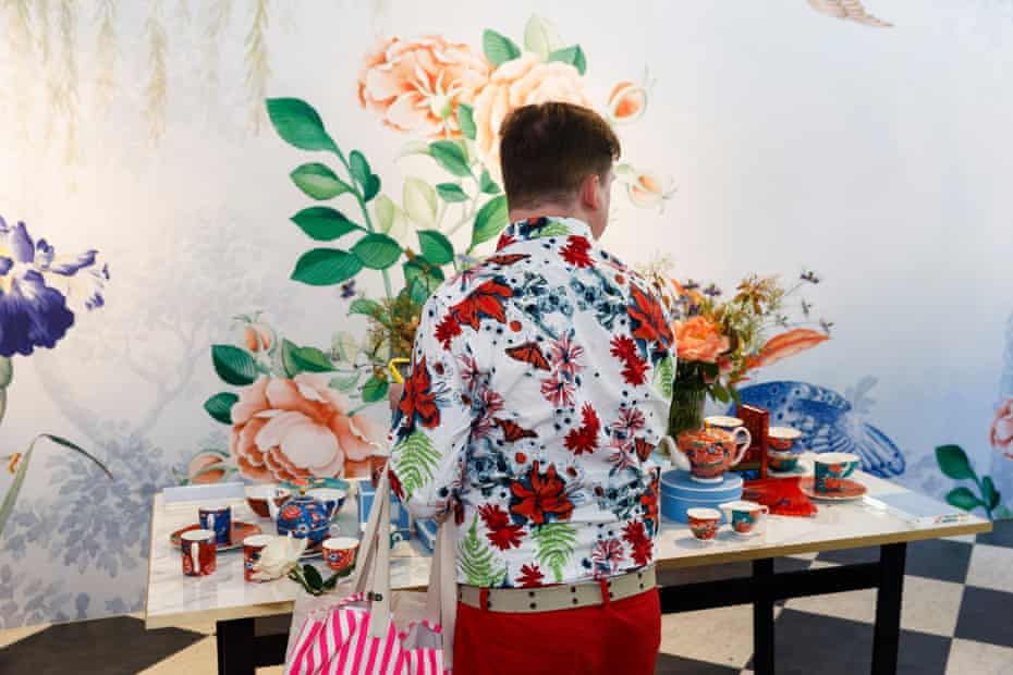 A man in a floral shirt studies Wedgwood pottery