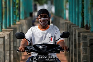 A man riding a motorbike in Jakarta, Indonesia, sports a smiley face mask