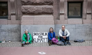 Benjamin Wagner (right) sits on the pavement with Greta Thunberg and a young boy with a sign about her climate strike
