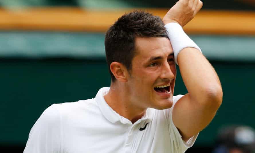 Bernard Tomic wipes his face during his match against Novak Djokovic at Wimbledon on Friday.