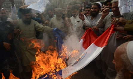 Protesters burn a representation of the French flag in Peshawar, Pakistan