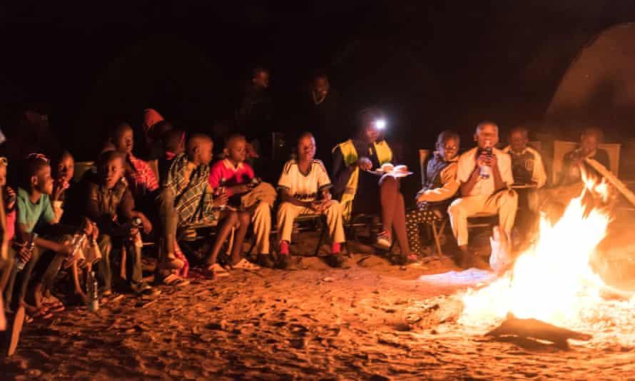 Children round a camp fire in Samburu National Reserve, Kenya during a visit to celebrate World Elephant Day 2016.