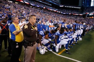 Colts players stand and kneel while officials observe the anthem in the traditional manner.