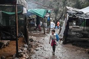 A young girl walks the muddy alleyways of the camp outside Moria