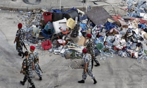 Lebanese policemen pass by a pile of rubbish on Monday, a day after violent protests against the ongoing trash crisis.