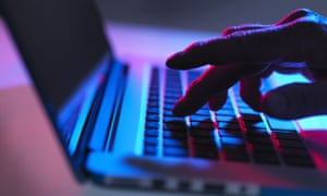 Silhouette of male hand typing on laptop