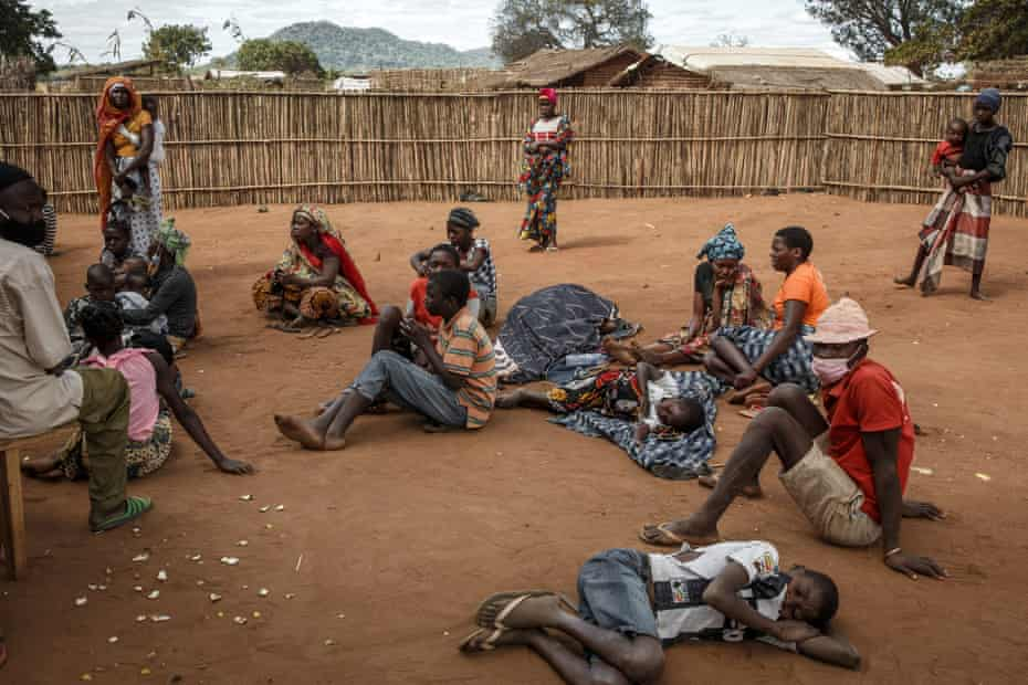 Displaced people sit and lie outside tents.