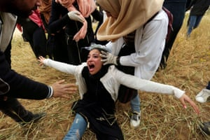A Palestinian woman reacts after inhaling teargas fired by Israeli forces at demonstrators marking Land Day and the first anniversary of a surge of border protests at the Israel-Gaza border in the southern Gaza Strip.