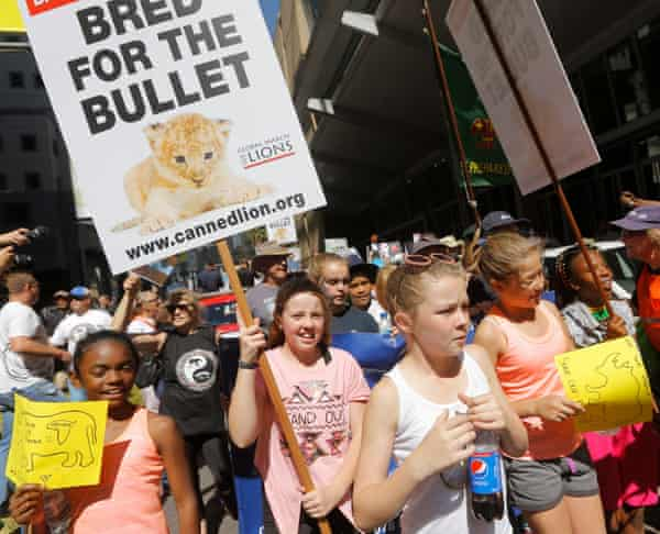 Animal rights activists carry placards outside the Sandton convention centre in Johannesburg, where the Cites summit is being held.