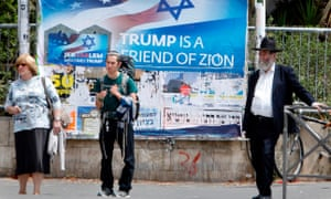 Israelis walks past a poster welcoming and supporting the US president in downtown Jerusalem.