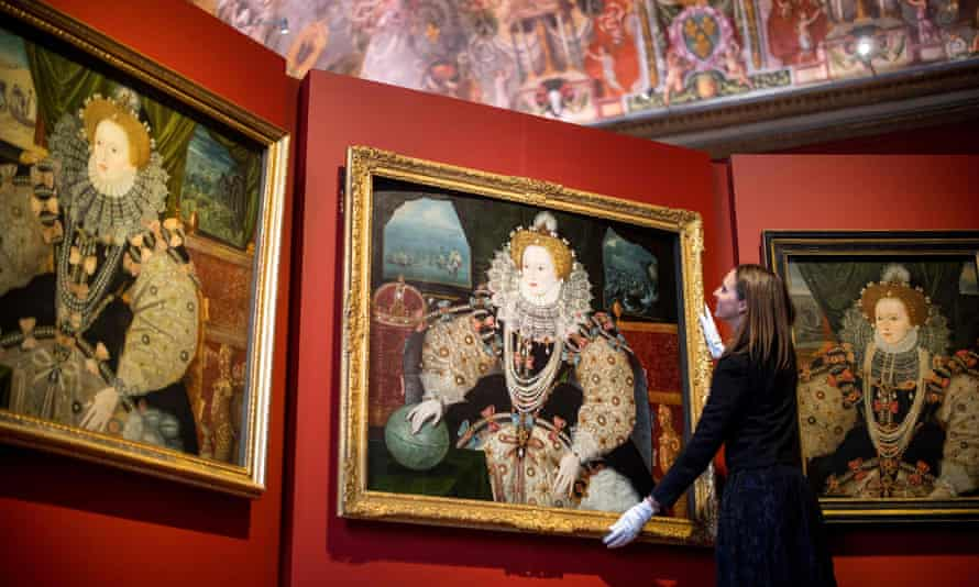 Royal Museums Greenwich curator Allison Goudie adjusts one of the Armada portraits before the opening of the Faces of a Queen exhibition.