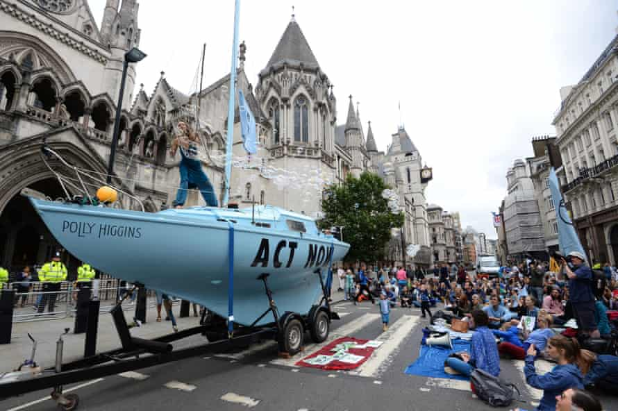 Protesters from Extinction Rebellion with a boat that has been parked outside the Royal Courts of Justice in London.