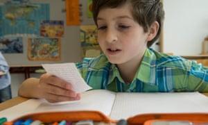 Schoolboy reading a message in classroom
