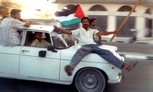 Palestinians speed through Gaza City by car.