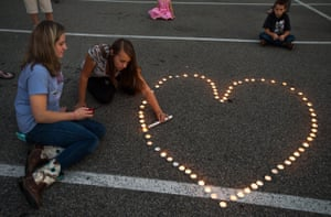 Community supporters light candles in the shape of a heart during a vigil for the two journalists.