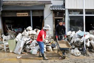 People clear debris from damaged shops in Hitoyoshi in Kumamoto prefecture