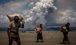 Rohingya refugees walk on the shore after crossing the Bangladesh-Myanmar border by boat