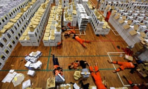 Workers lie down during a break as they prepared election materials in a warehouse in Jakarta on 15 April.