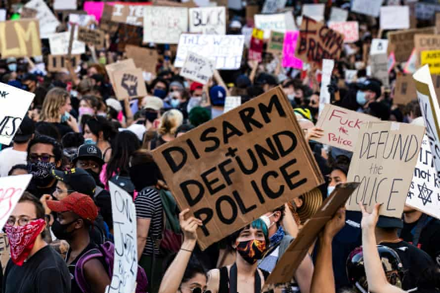 Protesters carry signs as they gather near city hall in Los Angeles on 3 June 2020.