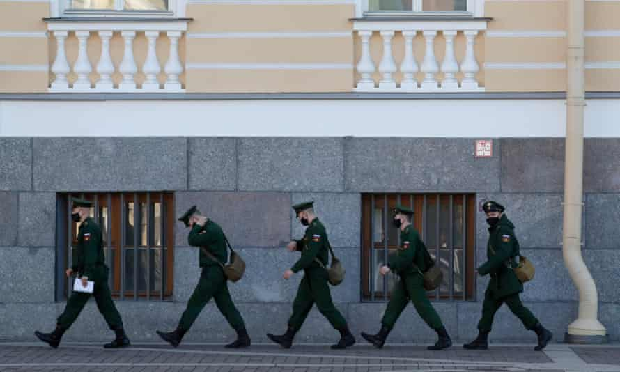 Russian soldiers wearing protective face masks walk along the Dvortsovaya square in St Petersburg.