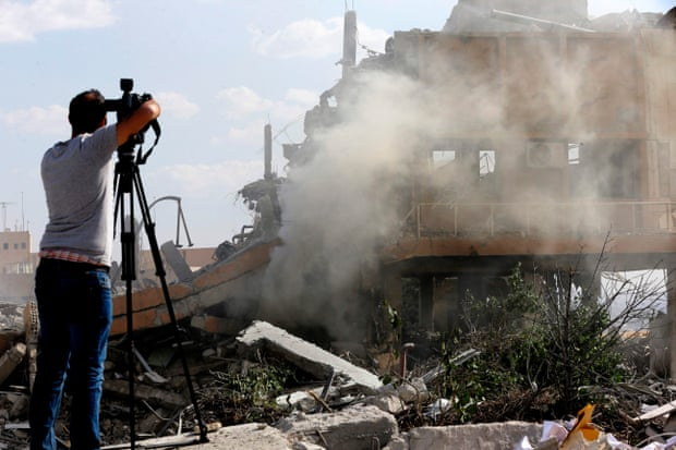 A journalist films the wreckage of the Scientific Studies and Research Centre in Barzeh, southern Syria in 2018.