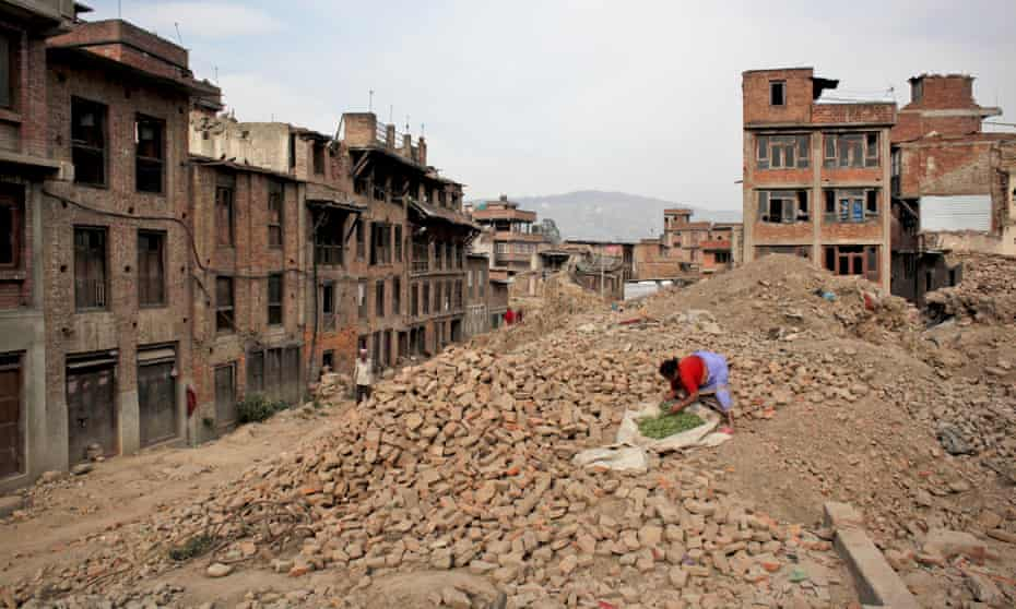 A woman dries vegetables on the rubble of a building damaged in the 2015 earthquake in Nepal.