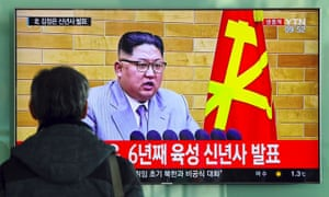 A man watches a television news broadcast showing North Korean leader Kim Jong-Un's New Year's speech