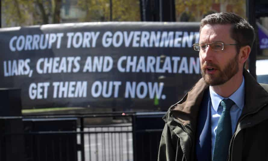 Simon Case in front of a banner reading 'Corrupt Tory government – liars, cheats and charlatans –get them out now.'