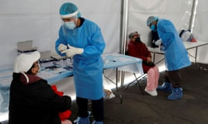 Healthcare workers wearing personal protective equipment (PPE) give instructions before they take a swab sample from women for coronavirus disease (COVID-19) rapid antigen testing outside the Azteca stadium in Mexico City, Mexico, November 25, 2020.